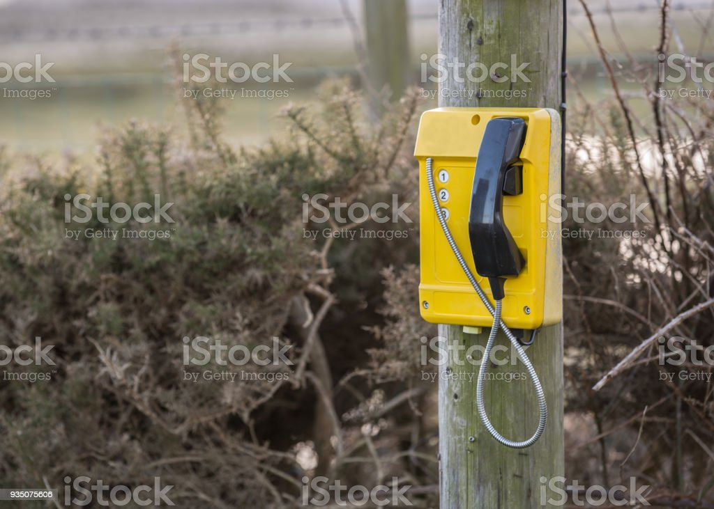 Emergency outdoor yellow fixed line phone on a timber post