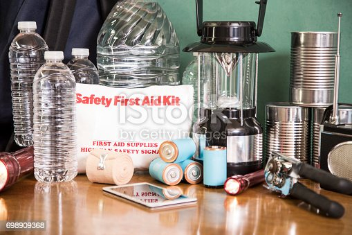 A pile of emergency preparation, natural disaster supplies including: flashlight, first aid kit, cell phone, lantern, water bottles, canned goods, can opener, radio, backpack, batteries.  It's hurricane season; be prepared.