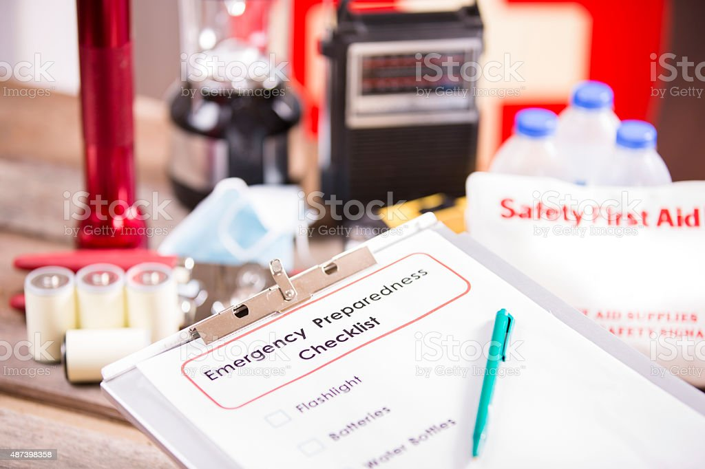 Emergency preparedness checklist on clipboard and a pile of supplies...