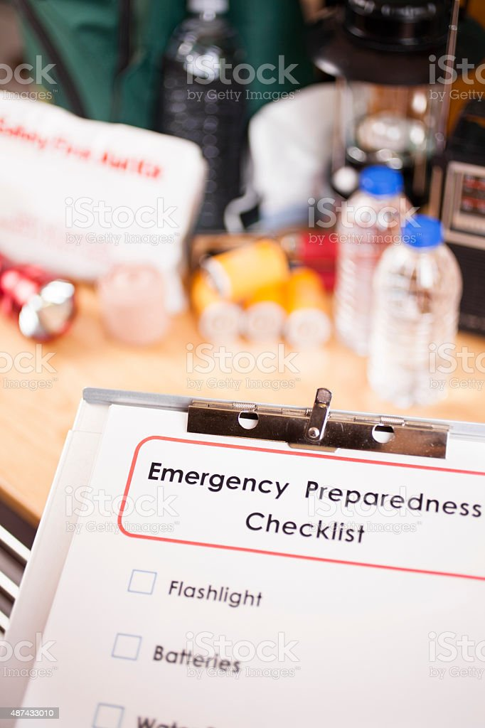 Emergency preparedness checklist on clipboard and a large pile of...