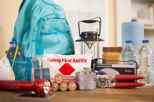 Emergency preparedness supplies.  A large collection of supplies to be used in case of a natural disaster (hurricane, flood, earthquake, etc) including flashlight, backpack, batteries, water bottles, first aid kit, lantern, radio, can opener and mask.  No People.