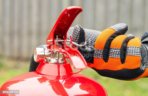 A man, wearing safety gloves, pulls the metal pin in preparation for using a fire extinguisher.