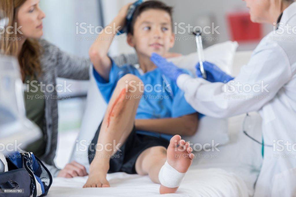 Salle d'urgence médecin examine un footballeur blessé - Photo