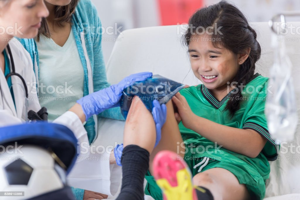 Elementary age soccer player grimaces in pain as ER doctor places...