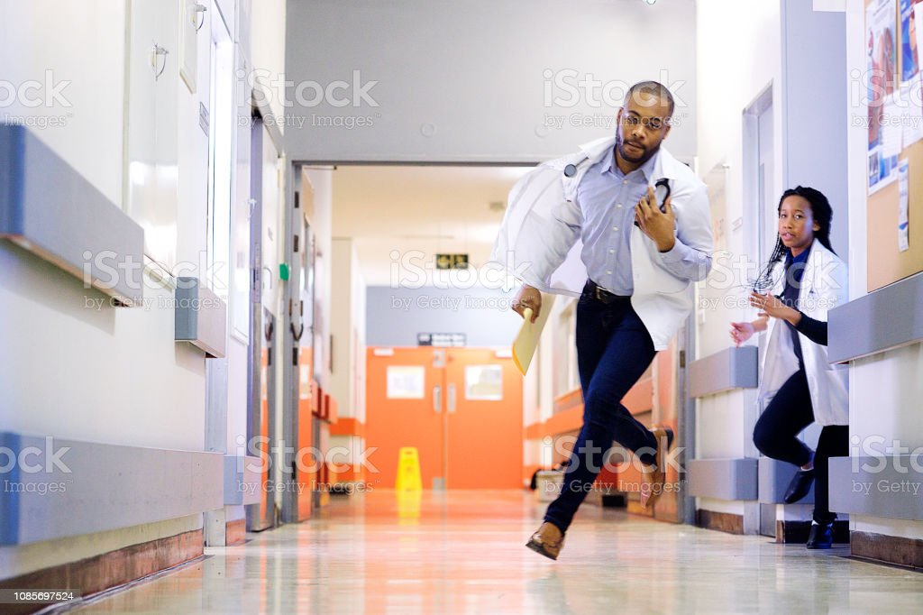 A male African-American young doctor comes running around the corner...