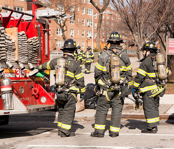 Emergency service. Fire-fighters next to fire-engine stock photo