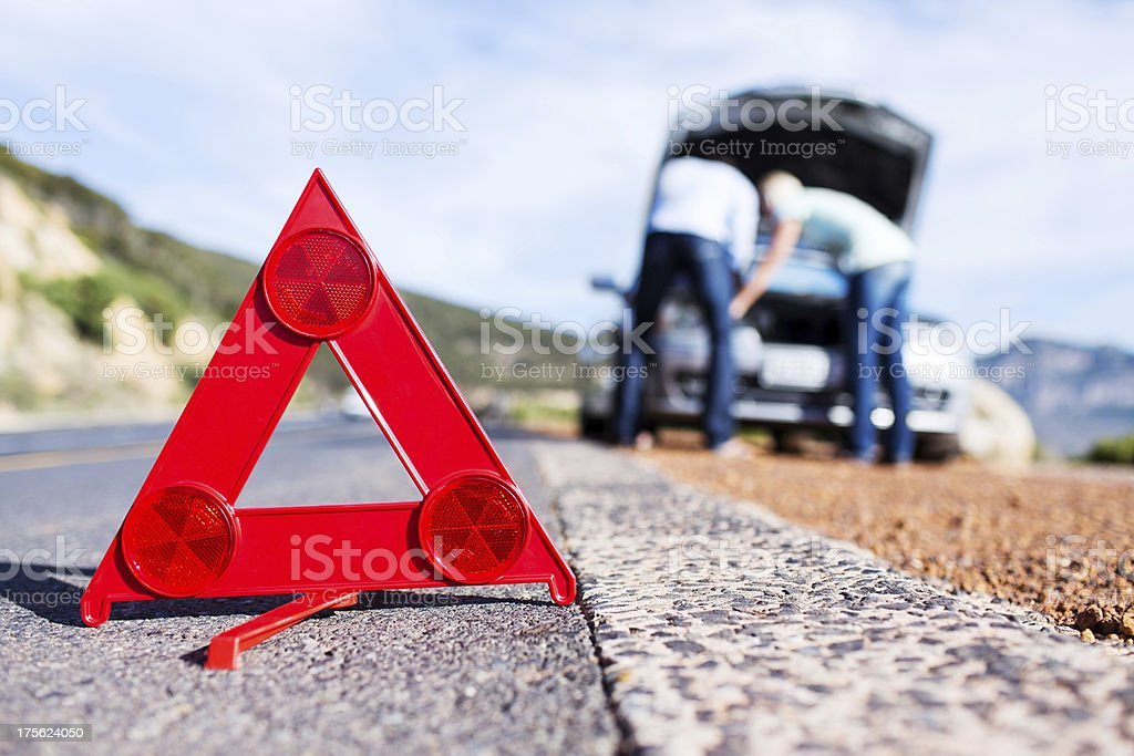 Emergency Sign Along Roadside With Couple Looking Under Car Hood stock photo