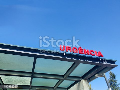 istock Emergency sign in red tone with blue sky in background. 1182986585