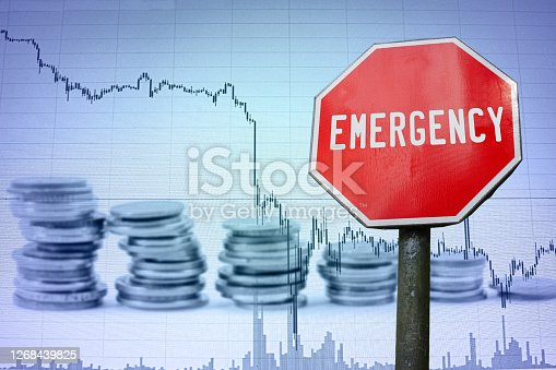 Emergency sign on economy background - graph and coins. Financial crash in world economy because of coronavirus. Global economic crisis, recession.