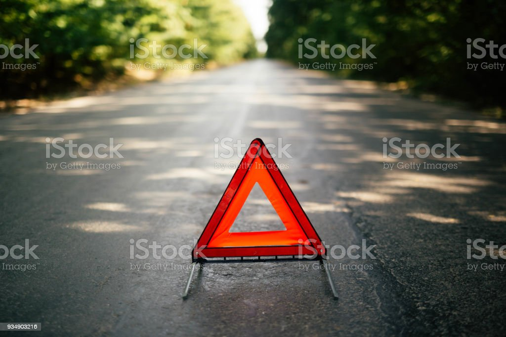 Blurry pose of a red emergency stop triangle sign has been put on the...