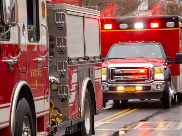 Emergency vehicles responding Ambulance and fire truck with lights flashing ambulance stock pictures, royalty-free photos & images