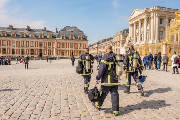 rettungsassistenten außerhalb des palastes von versailles. - französisch übungen stock-fotos und bilder