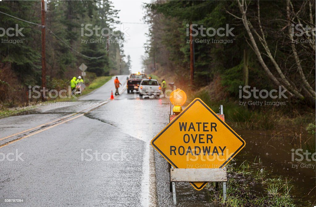 Emergency workers placing warning signs on flooded road stock photo
