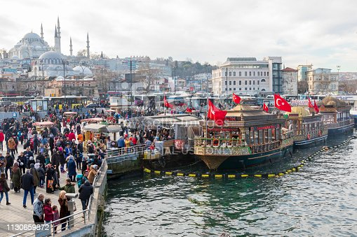 Istanbul, Turkey - Feb 01, 2019: Eminonu district with many facilities to eat such as floating restaurants and carts with fresh bakery, hot corn or roasted chestnuts in Istanbul, Turkey.