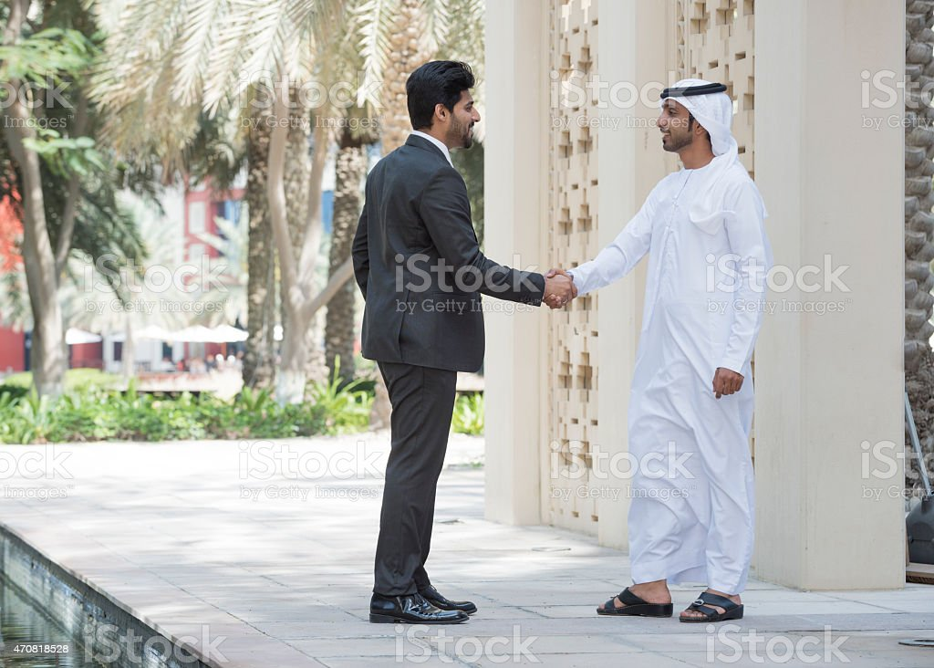 Emirati Arab man shaking hands with businessman outdoors stock photo