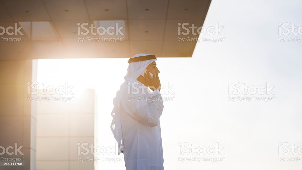 Emirati Businessman On A Rooftop In Evening Sunlight stock photo