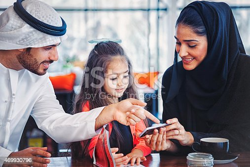 istock Emirati family enjoying with smartphone at cafe 469930796