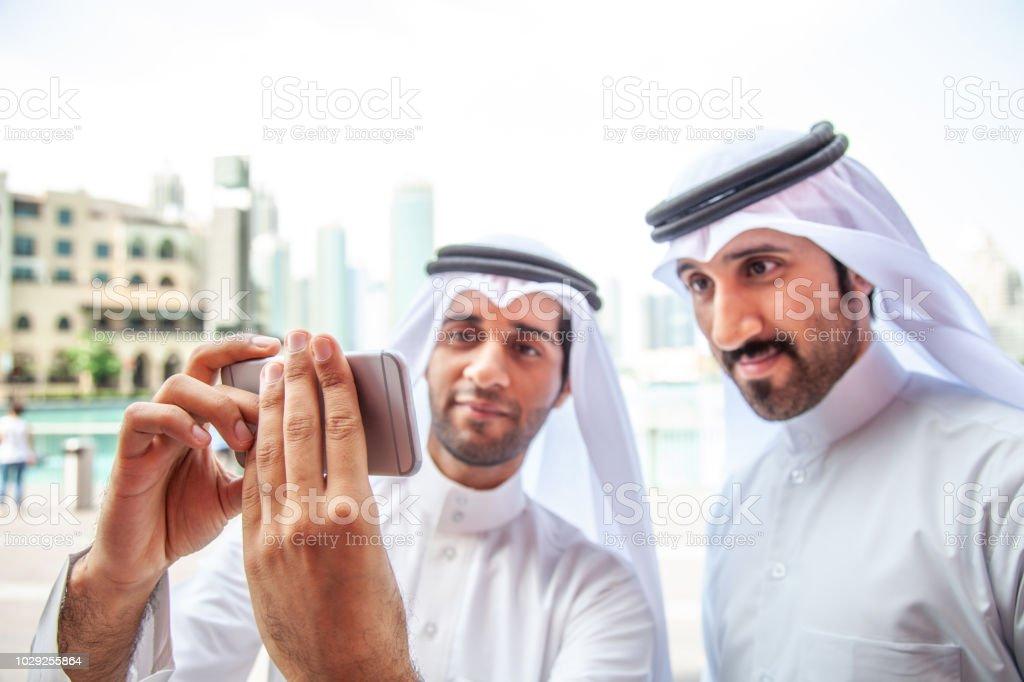 Emirati friends taking a selfie in Dubai downtown stock photo