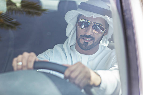 emirati man driving his car - styles stock photos and pictures