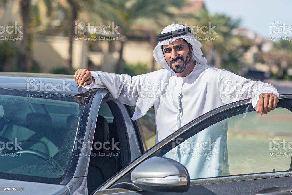 Emirati man getting on his car stock photo