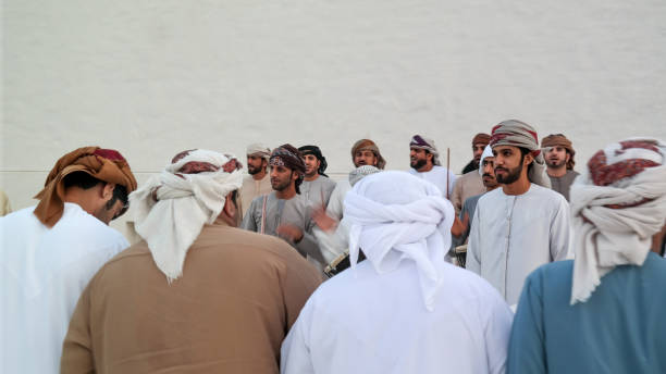 emirati (middle eastern) men performing a traditional dance in the heritage of the united arab emirates - the yowla - uae national day стоковые фото и изображения