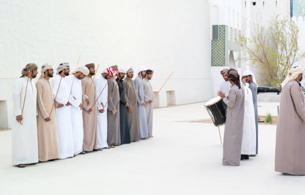 emirati men performing the yowla, a traditional dance in the heritage of uae - uae national day стоковые фото и изображения