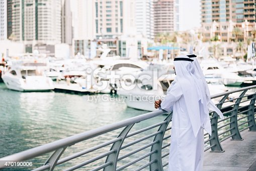 Two emirati men standing at the port and staring at yachts.
