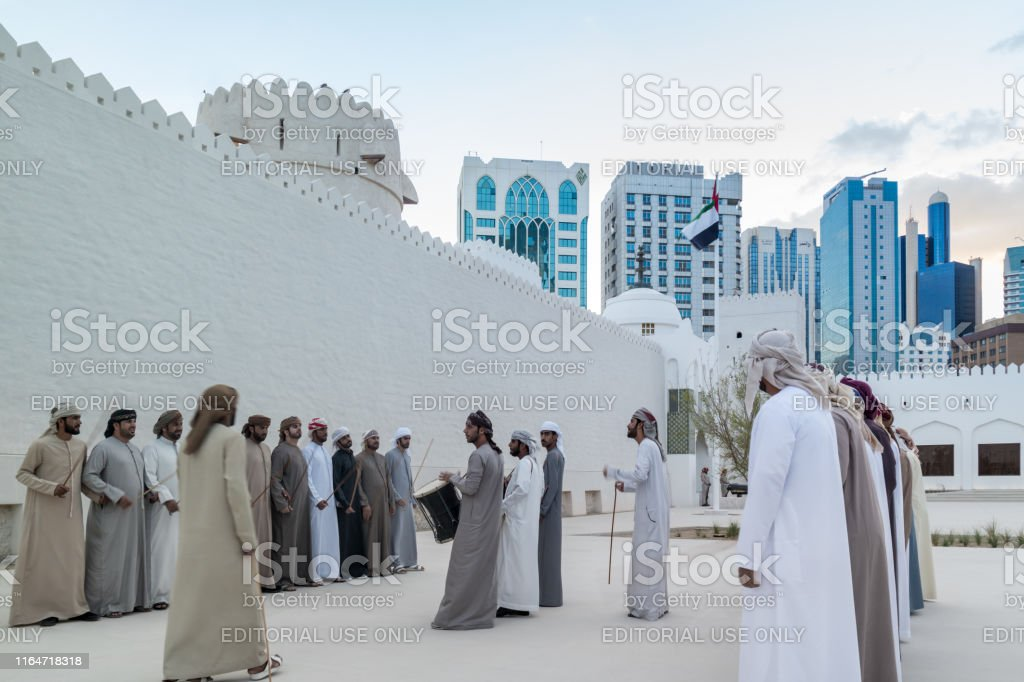 Emirati Middle Eastern Men performing a traditional dance (The Yowla) next to Al Hsin building, the United Arab Emirates - Zbiór zdjęć royalty-free (Abu Zabi)