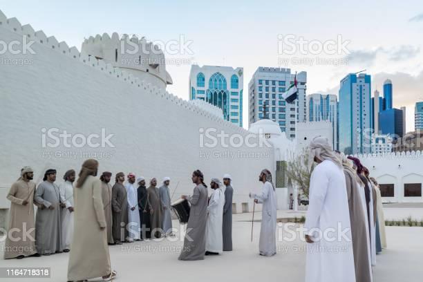 Emirati Middle Eastern Men Performing A Traditional Dance Next To Al Hsin Building The United Arab Emirates - zdjęcia stockowe i więcej obrazów Abu Zabi