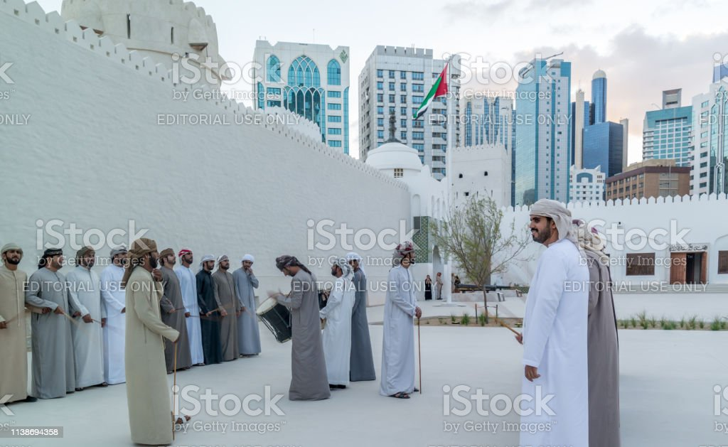 Emirati Middle Eastern Men performing the Yowla, a traditional dance in the culture of the United Arab Emirates - Zbiór zdjęć royalty-free (Abu Zabi)