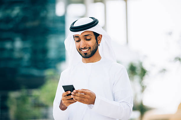 Emirati using a smart phone Emirati texting in Dubai middle eastern ethnicity stock pictures, royalty-free photos & images