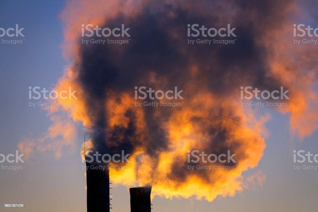 emisiones del tubo de la planta contra la puesta del sol - foto de stock