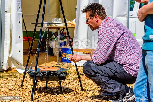 Emmaboda, Sweden - May 13, 2016: Forest and tractor (Skog och traktor) fair. Salesperson grilling some hot dogs for the visitors to come. Man kneeling beside the suspended barbeque.