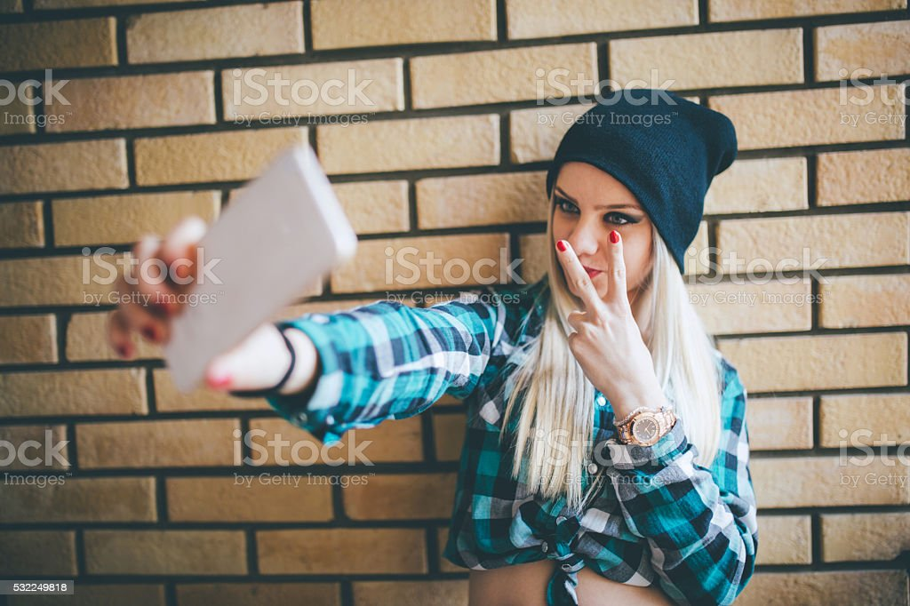 Emo girl taking selfie against brick wall stock photo