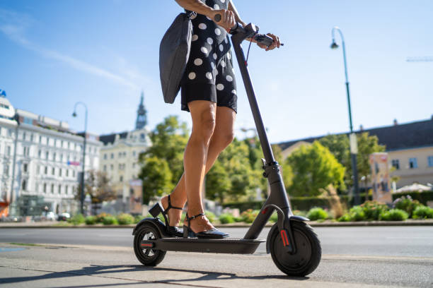 e-mobility commute to work, businesswoman on electric push scooter in city stock photo