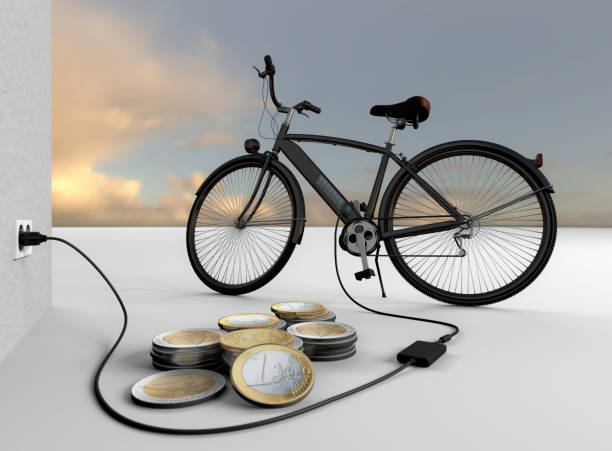 E-mobility. E-bike. How much does a full carge cost? An electric bicycle charges its batteries. Euro coins are in the foreground. electric bike charging stock pictures, royalty-free photos & images