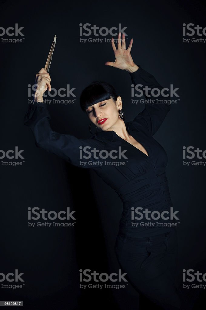 emotion brunette woman dance with a fan on black background royalty-free stock photo