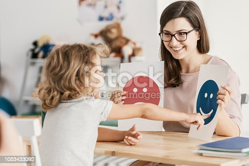istock Emotion emoticons used by a psychologist during a therapy session with a child with an autism spectrum disorder. 1053433092
