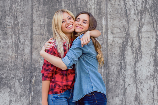 Emotion expressing summer punk holiday  vacation positive celebrate success toothy smile concept. Two beautiful cheerful excited girls wearing checkered shirt hugging isolated on concrete background