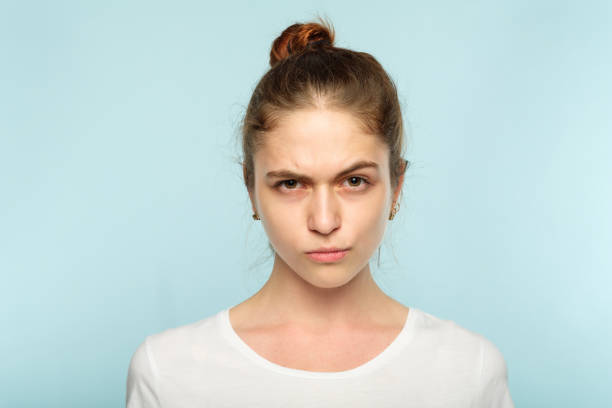 emotion frowning face grumpy pursed lips woman emotion face. frowning grumpy woman with pursed lips and piercing glance. young beautiful brown haired girl portrait on blue background. puckering stock pictures, royalty-free photos & images