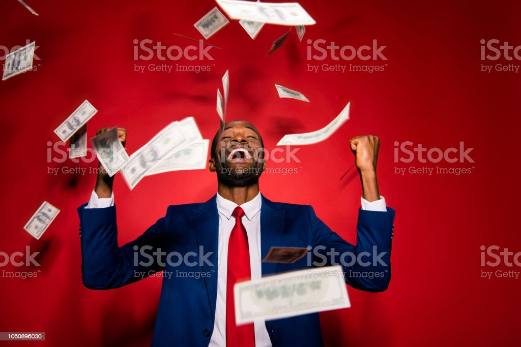 Emotion reaction concept. Crazy man in stylish trendy style formal wear tux tuxedo jacket suit tie close eyes raised fists up isolated on red bright background under money rain stock photo