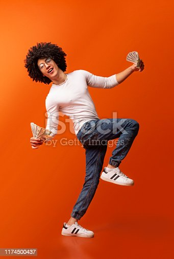 istock Emotional african man dancing with lots of dollars 1174500437
