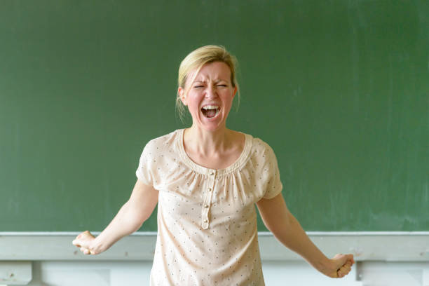 Emotional angry teacher yelling at her class stock photo