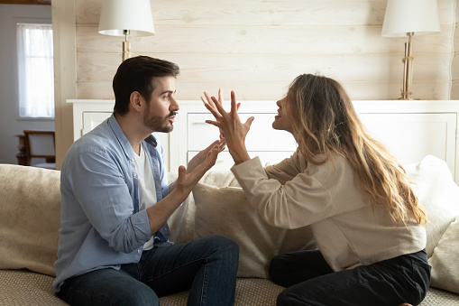Emotional annoyed stressed couple sitting on couch, arguing at home. Angry irritated nervous woman man shouting at each other, figuring out relations, feeling outraged, relationship problems concept.