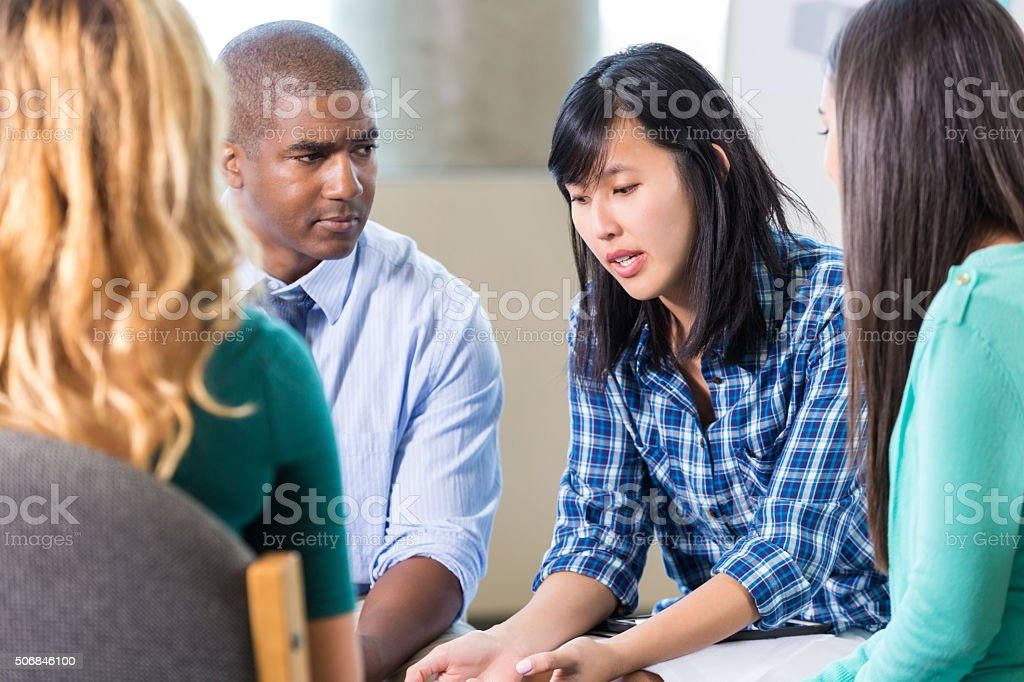 Emotional Asian woman talks in group therapy stock photo