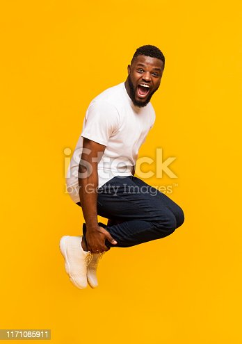 istock Emotional black guy jumping in bomb style and shouting 1171085911