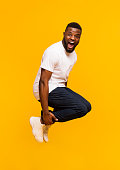 Emotional african american man jumping in bomb style and shouting, yellow studio background with free space