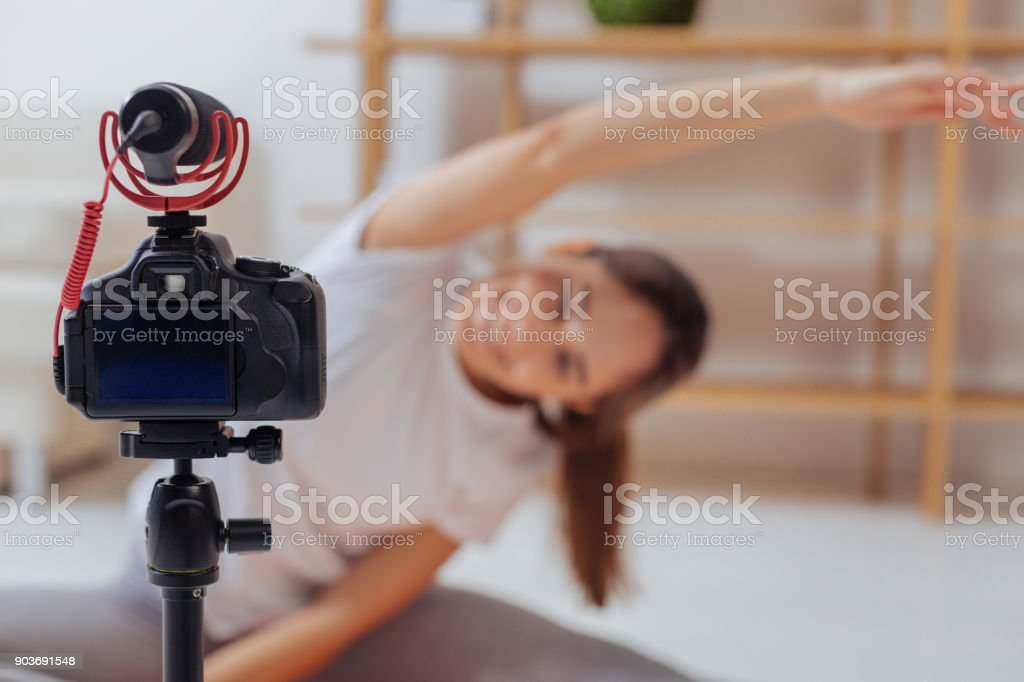 Emotional blogger exercising in front of a camera and feeling happy stock photo