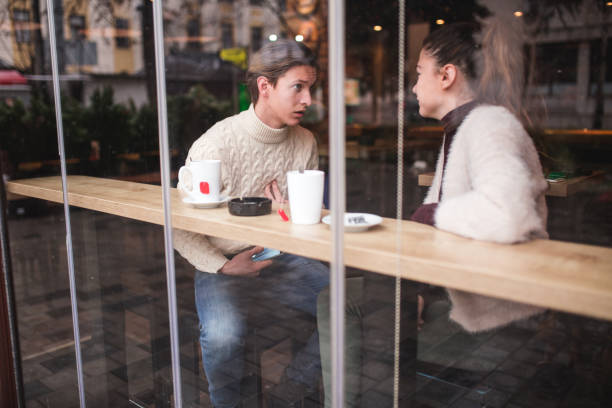 Emotional Break Up While Young Man Is Explaining Himself To His Girlfriend, Catching Her And Begging For Forgiveness She Answers bad date stock pictures, royalty-free photos & images