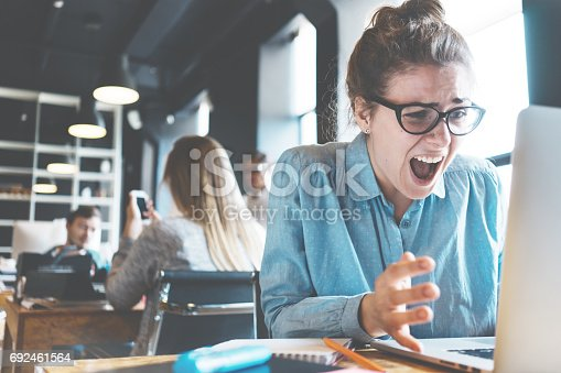 692461598 istock photo Emotional business lady shouting at her laptop 692461564